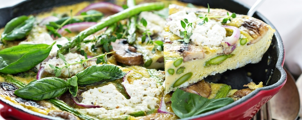 asparagus and goat cheese frittata sitting in a cast iron skillet